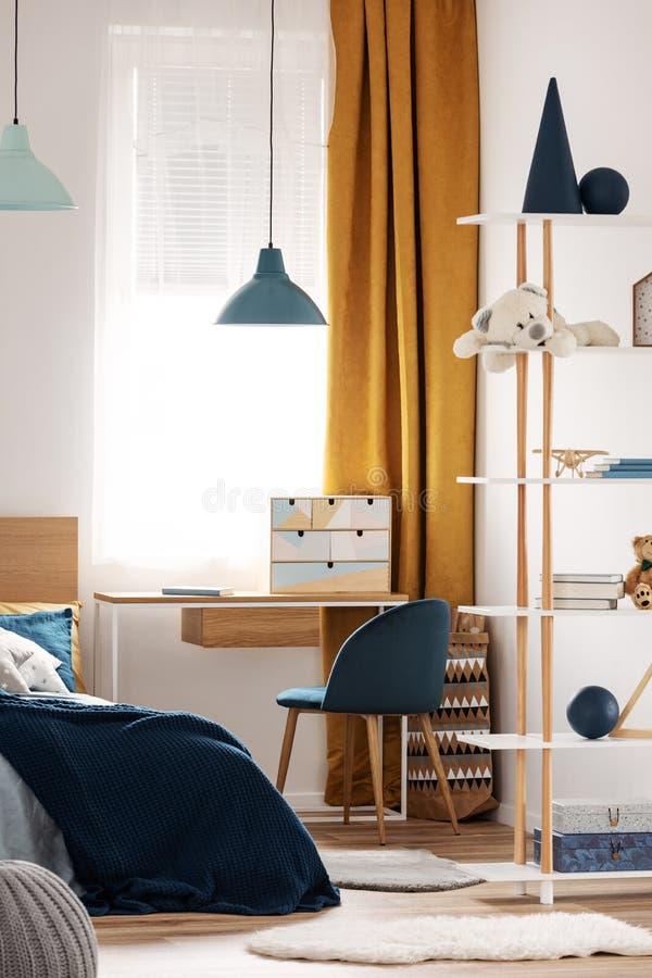 书桌、椅子和单人床与蓝色卧具在舒适卧室内部为孩子 免版税库存照片