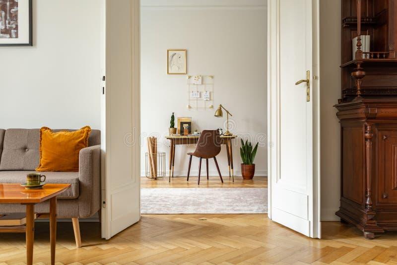 书桌和椅子在家庭办公室内部 看法通过葡萄酒客厅的门 实际照片 图库摄影