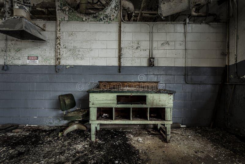 书桌和椅子被放弃的工厂 库存图片