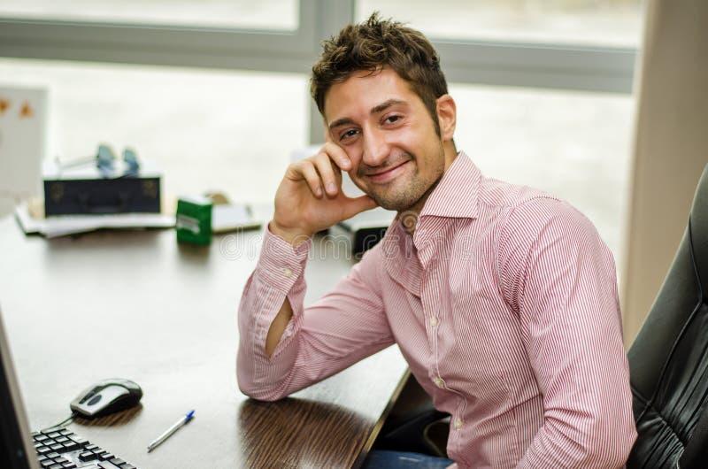 书桌工作的微笑的男性办公室工作者 免版税库存照片