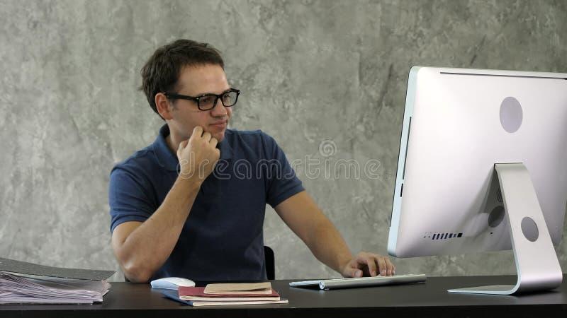 书桌的乏味年轻人在计算机前面 图库摄影