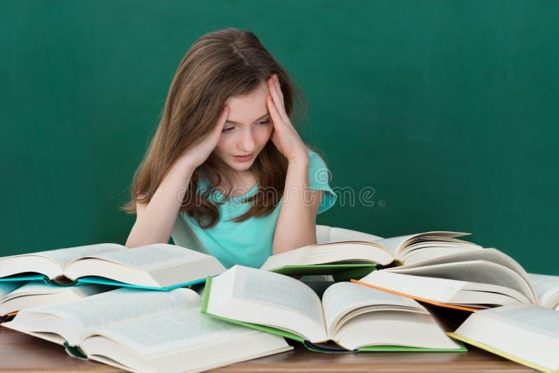书桌的女孩有许多书的 免版税图库摄影