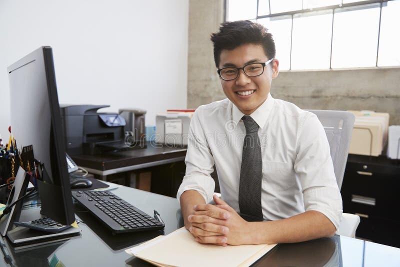 书桌的年轻亚裔男性专家微笑对照相机的 免版税库存图片