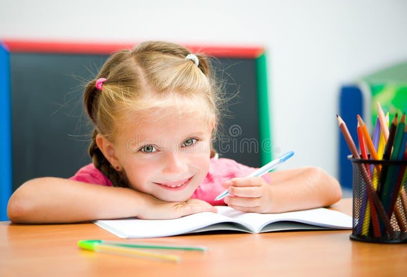书桌的美丽的小女孩 免版税库存照片