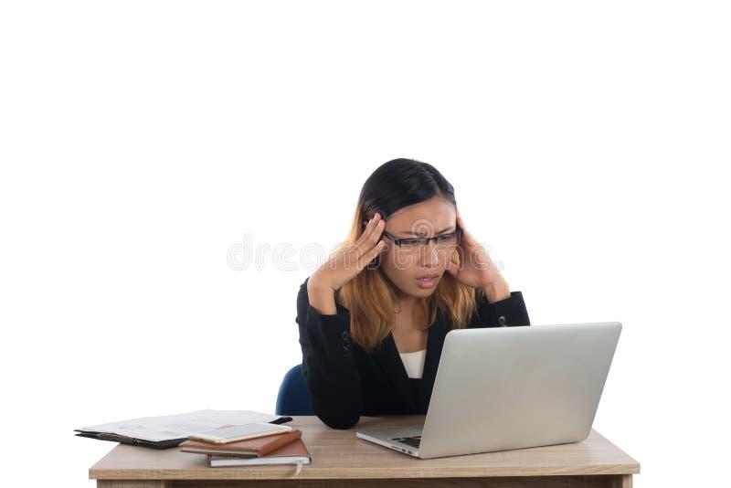书桌的被注重的年轻女商人有被隔绝的膝上型计算机的 免版税库存图片