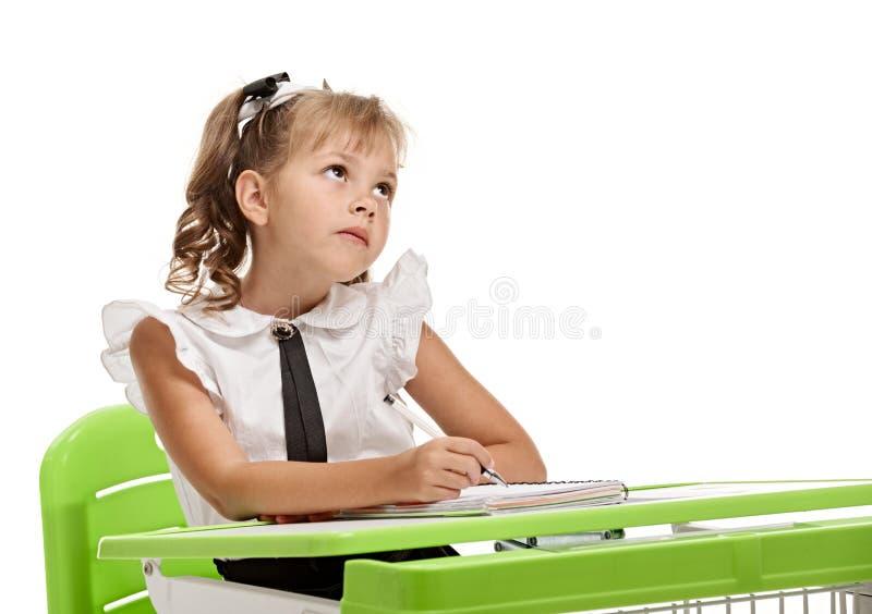 书桌的重视的女小学生 免版税库存照片
