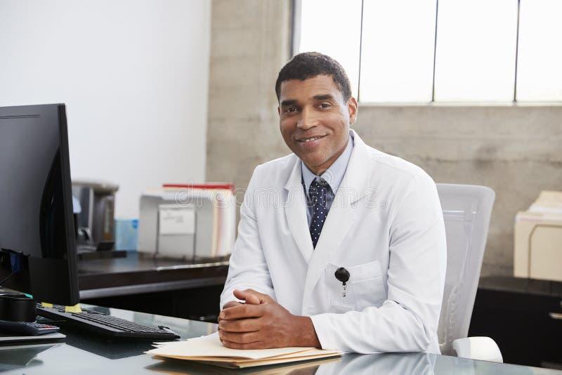 书桌的,画象混合的族种男性医生 免版税库存图片