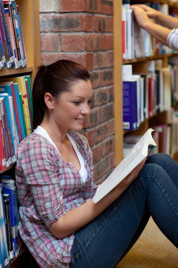 书楼层俏丽的读取妇女年轻人 免版税库存照片