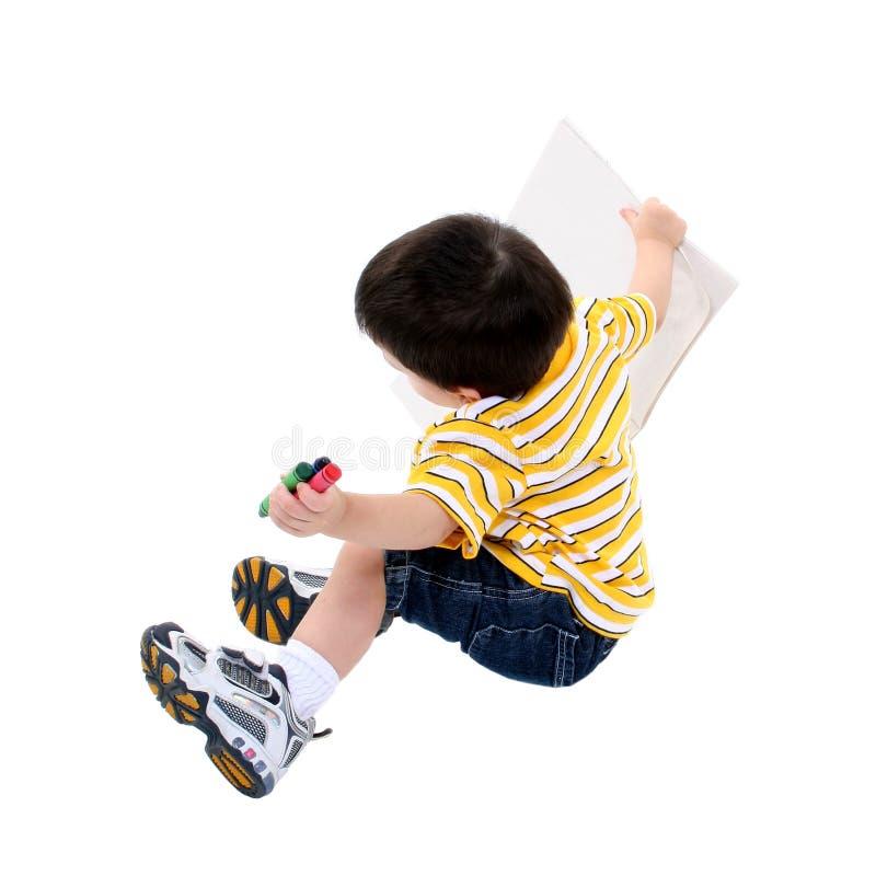 书男孩着色用蜡笔画庞然大物 免版税库存照片