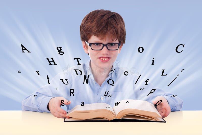 书男孩逗人喜爱的服务台他的读取 免版税库存图片