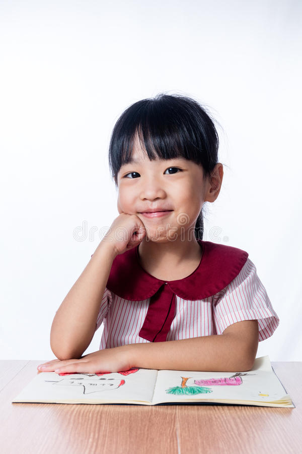 读绘画书的亚裔矮小的中国女孩 库存照片
