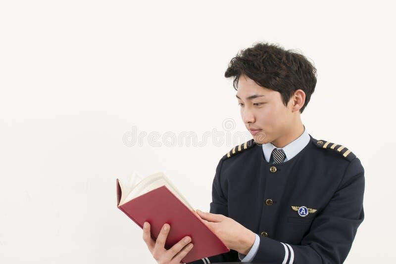 读书的亚洲航空公司飞行员 免版税库存照片