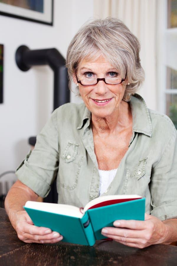 读书的可爱的年长妇女 免版税库存图片