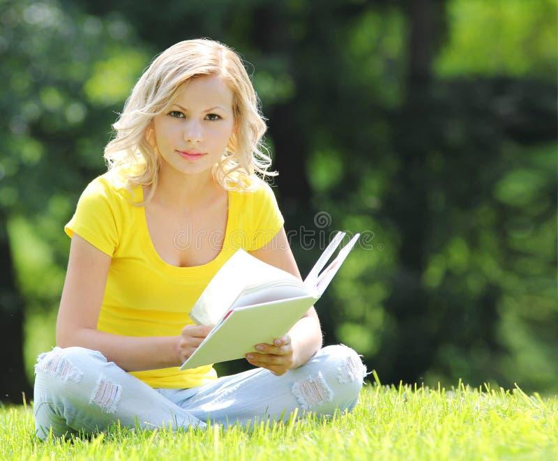 读书的女孩。有书的白肤金发的美丽的少妇坐草。室外。晴天。看照相机 库存图片