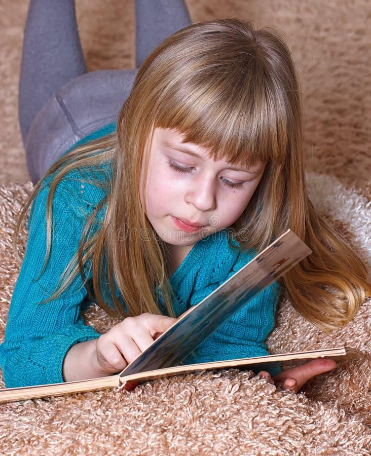 读书的女孩,当说谎在地毯时 免版税库存图片