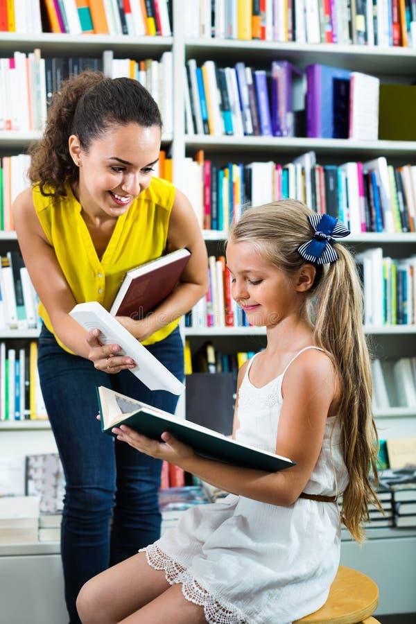 给书的妇女入学年龄的女孩在书店 免版税库存图片
