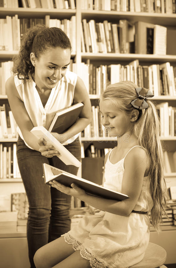 给书的妇女入学年龄的女孩在书店 免版税库存照片