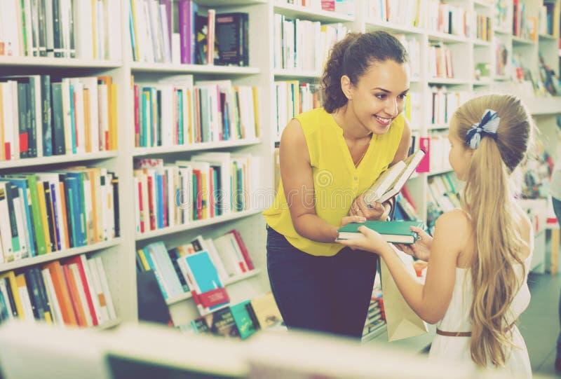 给书的妇女女孩在商店 免版税库存照片