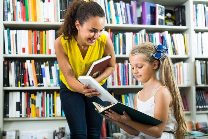 给书的妇女女孩在商店 库存照片