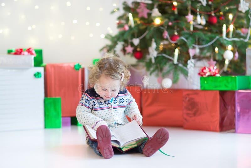 读书的小愉快的小孩女孩在一棵美丽的圣诞树下 免版税库存照片