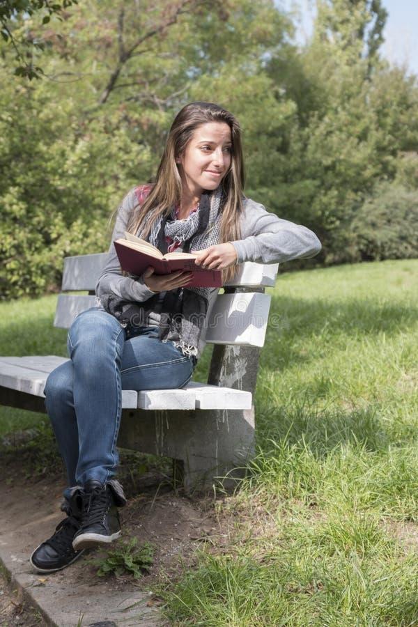 读书的少妇在公园长椅 免版税库存图片