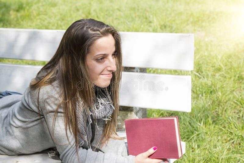读书的少妇在公园长椅 图库摄影