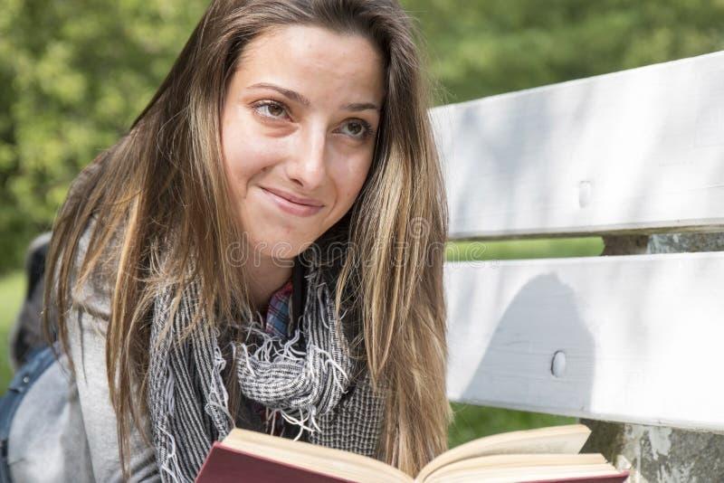 读书的少妇在公园长椅 免版税库存照片