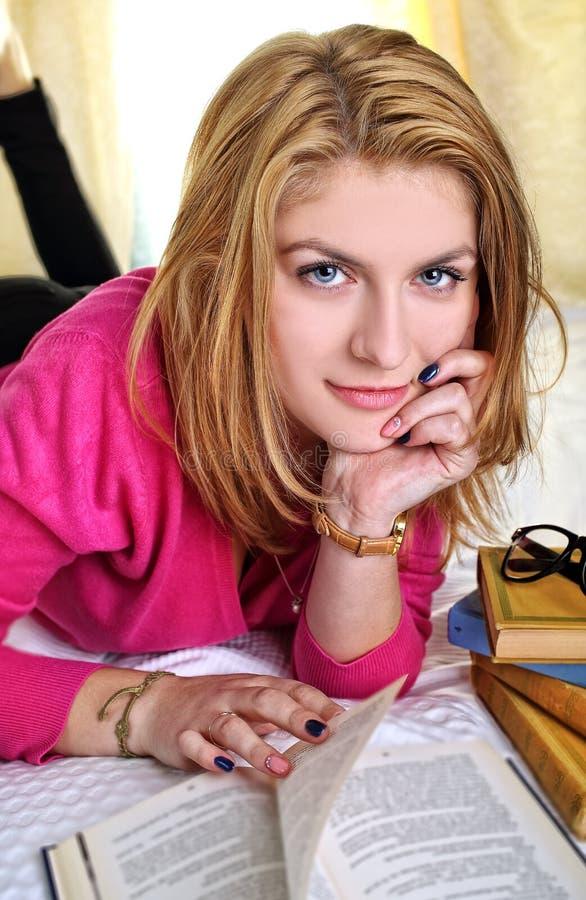 读书的微笑的学生女孩 库存照片