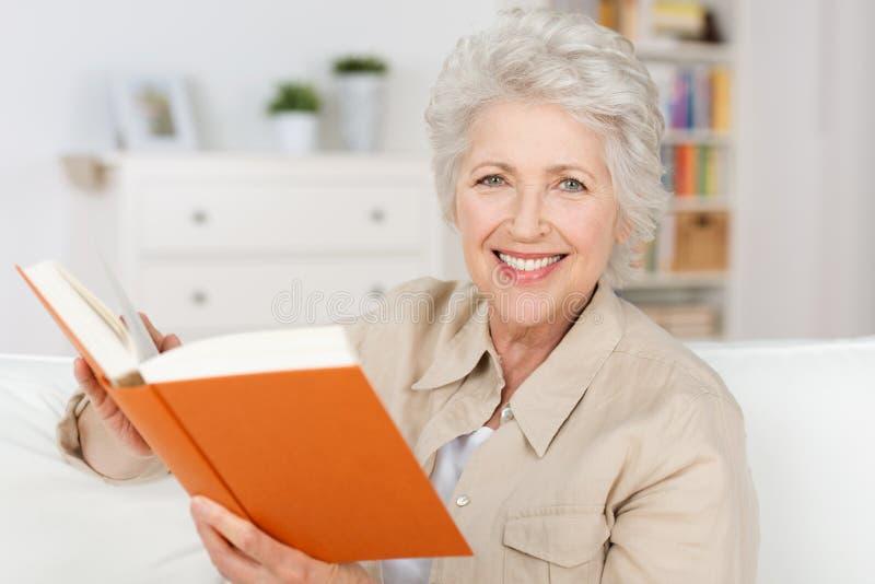 读书的微笑的年长夫人 免版税图库摄影