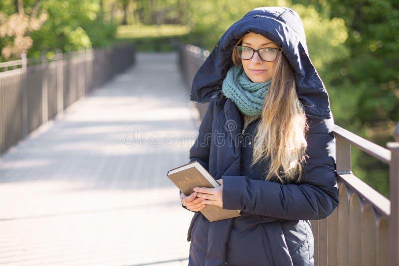 读书的愉快的女孩在栏杆 免版税库存图片