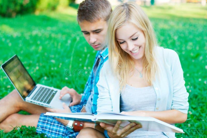 读书的愉快的女孩户外 免版税库存照片