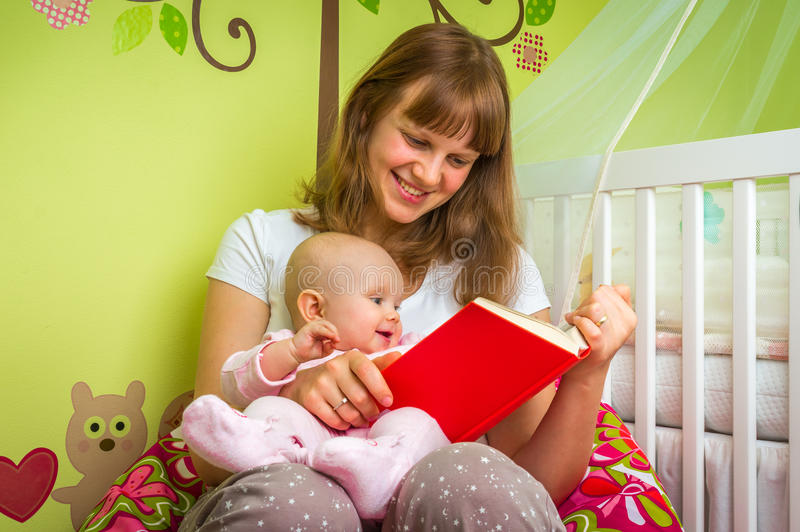 读书的愉快的母亲对她的女婴 免版税库存图片
