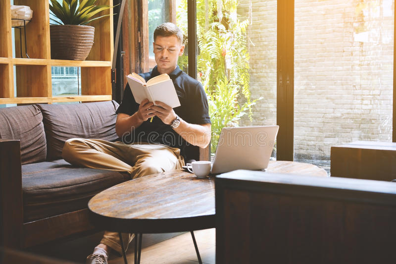 读书的愉快的英俊的年轻人 免版税库存照片
