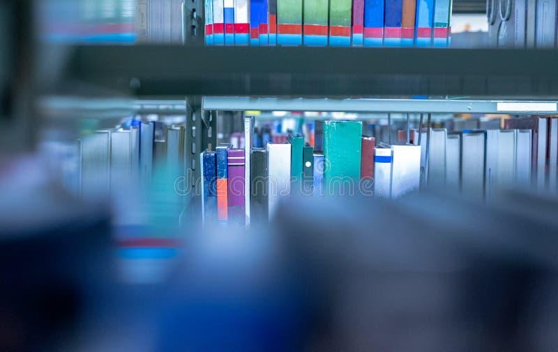 书的模糊的照片在一本被堆积的书打开在有书架的图书馆里作为背景 免版税库存图片