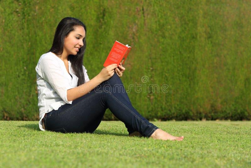 读书的美丽的阿拉伯妇女坐草坪在公园 免版税库存图片
