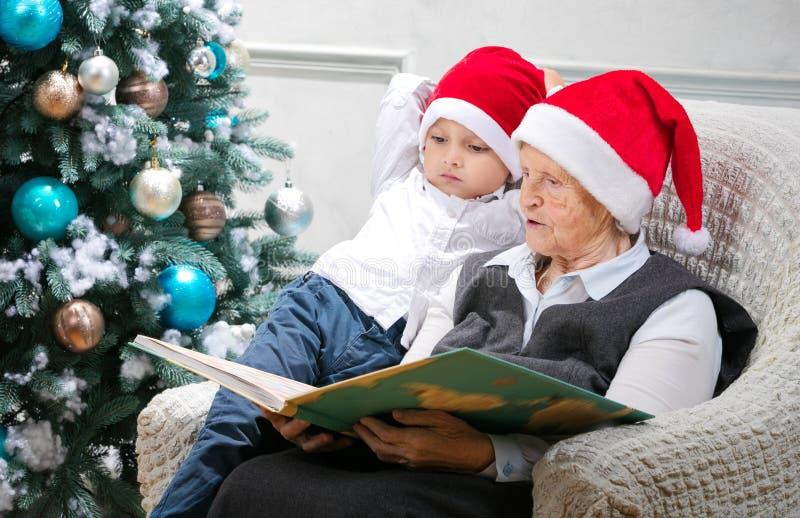 读书的资深妇女对她的孙子 免版税库存图片