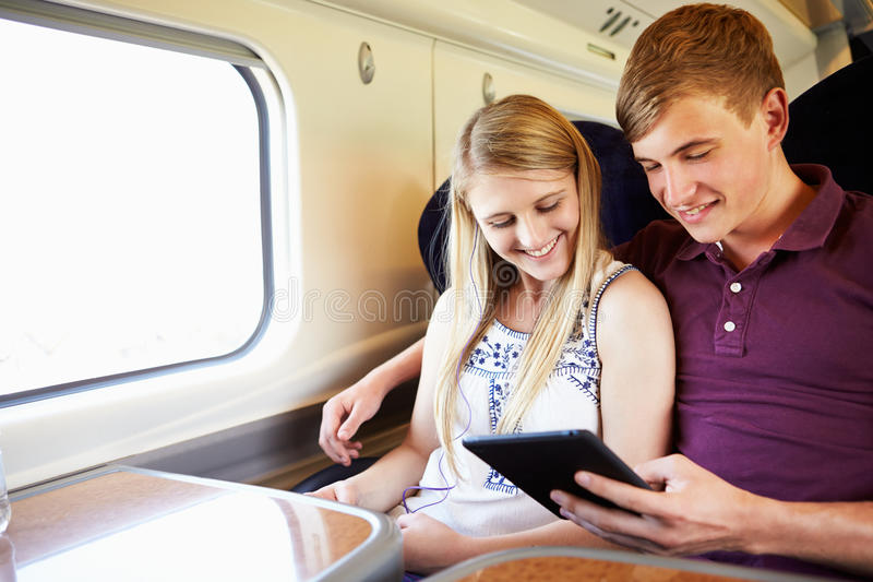读书的年轻夫妇在列车行程 免版税库存图片