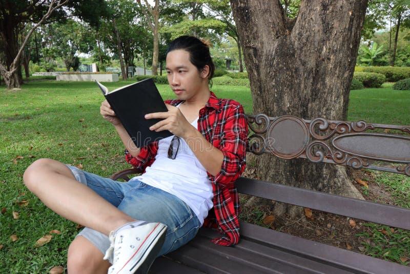 读书的年轻轻松的人画象在长凳在美丽的室外公园 免版税库存图片
