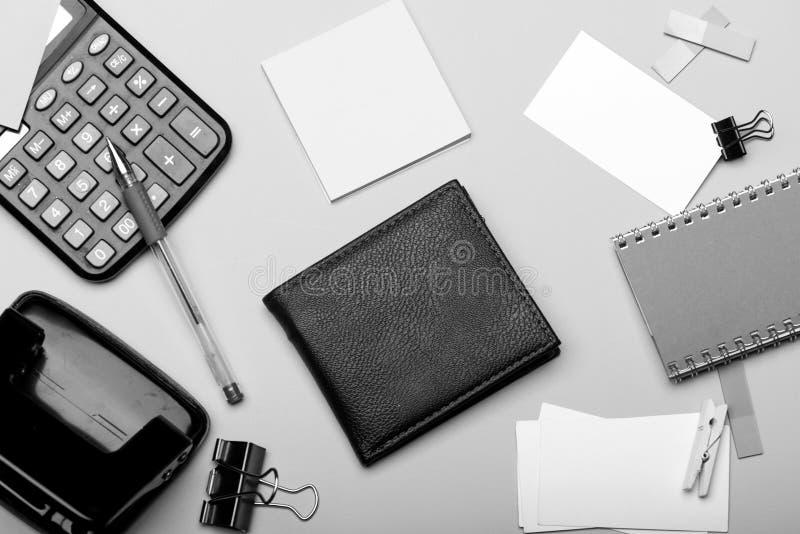 书签、灰色笔记本、打孔器、晒衣夹和笔在深蓝蓝色背景 文具、钱包和计算器 图库摄影