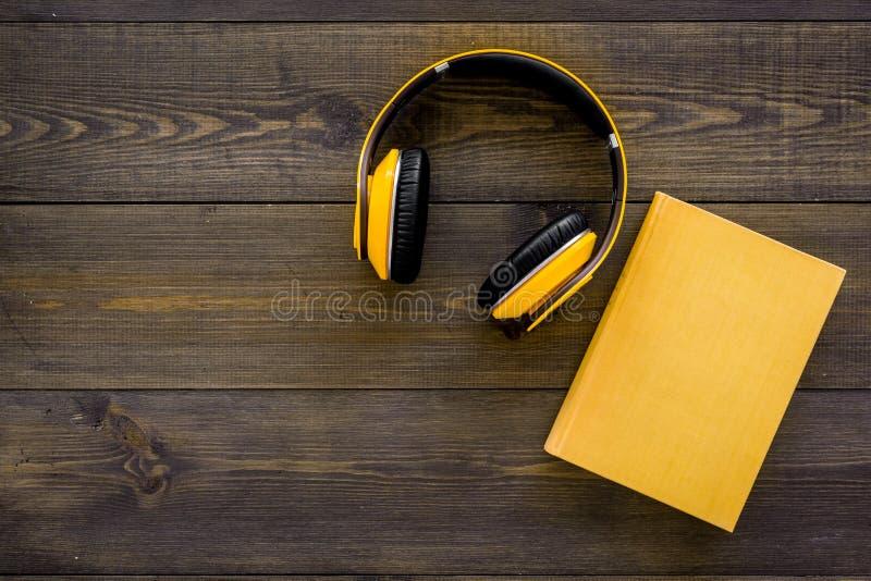 书网上概念, audiobooks 花费leasure时间读书和听的音乐 耳机临近精装书书与 库存照片