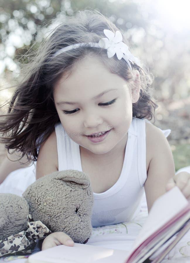书逗人喜爱的女孩读取 免版税图库摄影