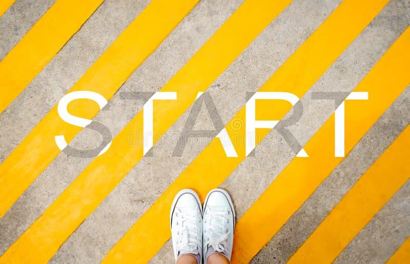 书面的脚和词开始柏油路背景 从上面看的脚和腿 站立Selfie白色鞋子的运动鞋  免版税库存图片