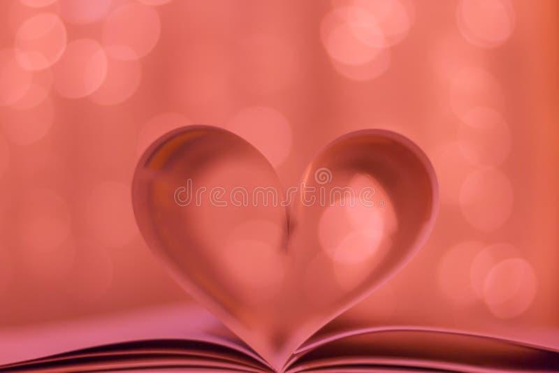书页把变成心脏形状和被弄脏的bokeh背景 概念亲吻妇女的爱人 库存图片