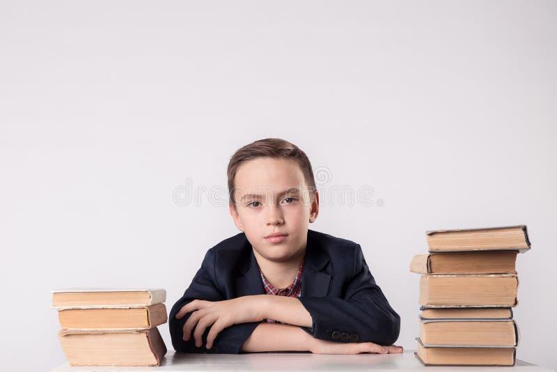 书,学校,孩子 拿着书的小学生 有书的滑稽的疯狂的男孩 库存照片