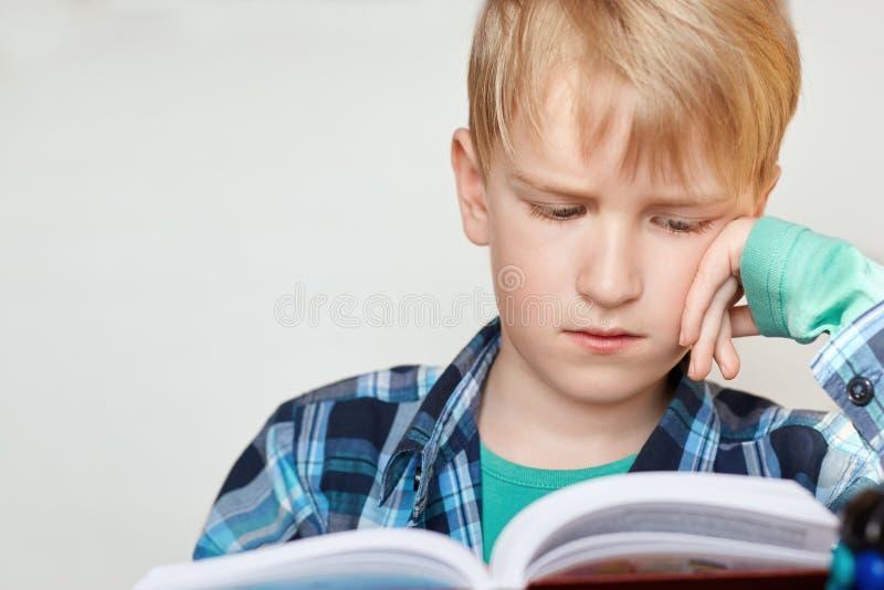 书,学校,孩子 有金发的小男小学生在控制中衬衣选址和调查穿戴了疲倦明确的书 免版税库存图片