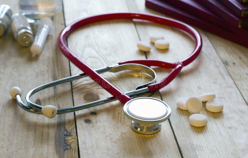 书,红色听诊器,药片 免版税库存照片