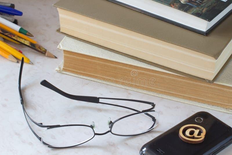 书,玻璃,上色了铅笔,在桌上的电话 库存图片
