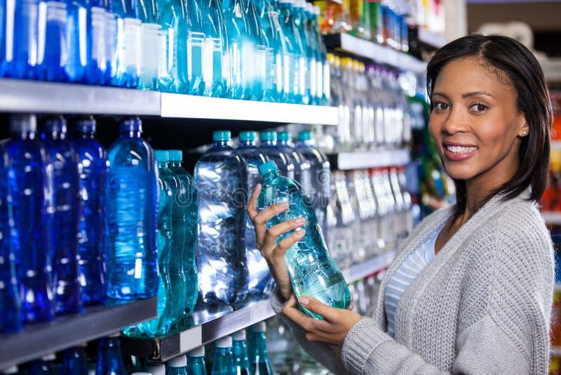 买一个瓶水的妇女 免版税图库摄影