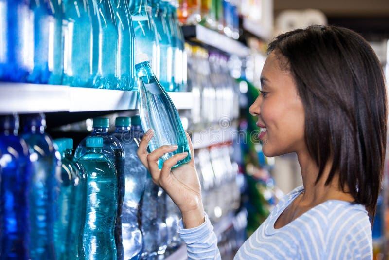 买一个瓶水的妇女 免版税库存图片
