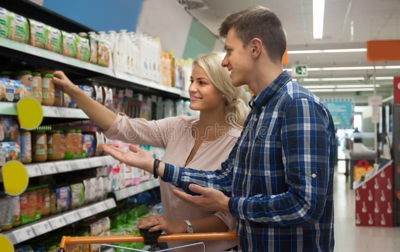 购买儿童食品的普通的家庭在大型超级市场 免版税库存图片